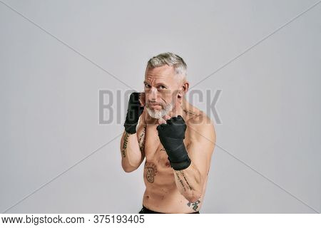Half Naked Middle Aged Athletic Man, Kickboxer Looking At Camera While Boxing, Practicing Punches In