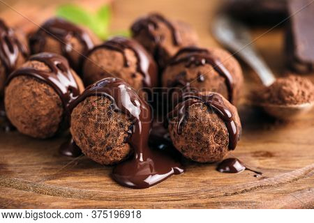 Homemade Chocolate Candy Truffles Glazed With Chocolate Ganache On A Wooden Board, Closeup View