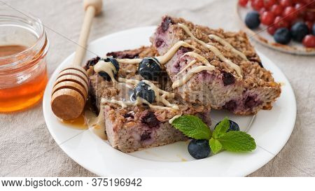 Vegetarian Baked Oatmeal With Blueberry Or Oat Protein Bars Served With Nut Butter. Closeup View. He