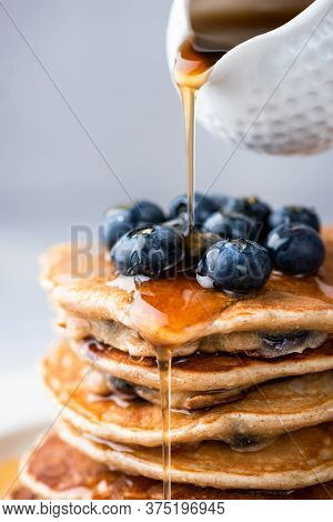 Maple Syrup Pouring On Stack Of Pancakes Closeup View. Sweet Golden Maple Syrup Pouring On Blueberry