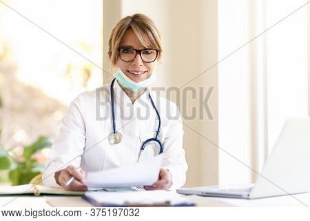 Smiling Female Doctor Sitting At Desk In Doctor's Office And Working