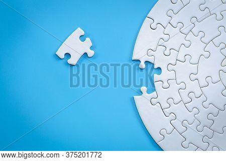 White Jigsaw Pieces On A Blue Background, Copy Space, Concept Image Of Unfinished Task.  Missing Jig
