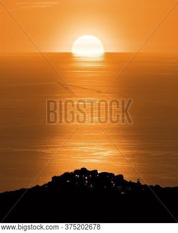 Sun Setting Over The Calm Mediterrnean Sea With The Silhouette Of The Hilltop Village Of Sant'antoni