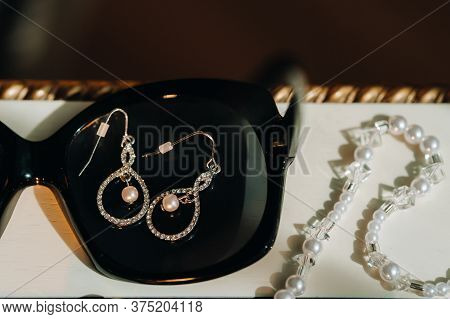 Accessories For The Bride. Earrings On A Black Background. White Wedding Earrings. Space For Text An