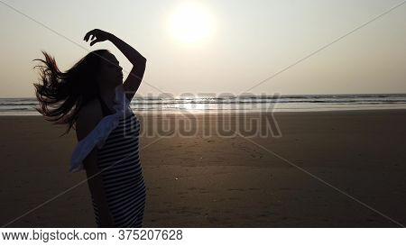 Relaxed Woman Stands, Straightening Her Hair On Shore. Portrait Of Pleasant Lady Spending Time Enjoy