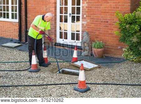 Buckingham, Uk - August 07, 2015. Man Jetting Sewage Drain Outside House, Drain Cleaning Company Unb