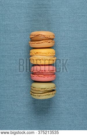 Four Delicious And Colorful Macaroonson Blue Vinyl Background.