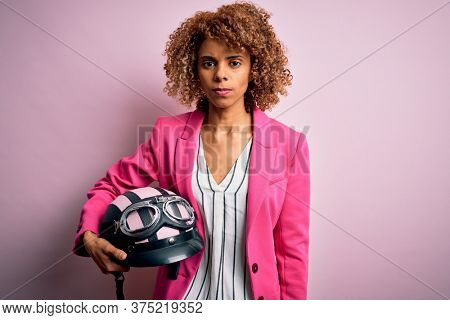 African american motorcyclist woman with curly hair holding moto helmet over pink background with a confident expression on smart face thinking serious