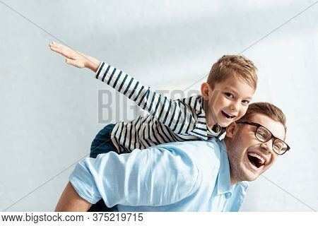Father Piggybacking Happy Son Looking At Camera And Imitating Flying