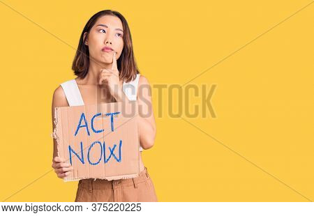 Young beautiful chinese girl holding act now banner serious face thinking about question with hand on chin, thoughtful about confusing idea