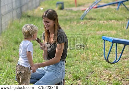 A Boy With Cochlear Implants Eating Ice Cream With His Mother