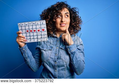 Young beautiful curly arab woman holding period calendar controlling menstrual cycle serious face thinking about question, very confused idea