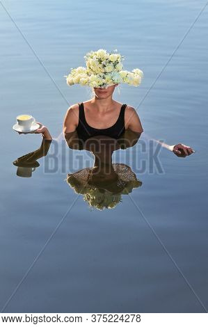 Young Woman With Flowers Hat Serving A Cup Of Coffee