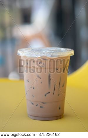 Cold Mocha Coffee Drink In Takeaway Glass On Yellow Table