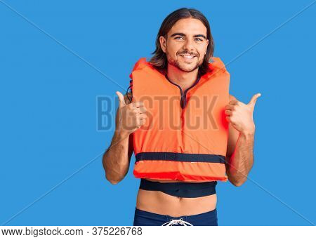 Young handsome man wearing nautical lifejacket success sign doing positive gesture with hand, thumbs up smiling and happy. cheerful expression and winner gesture.