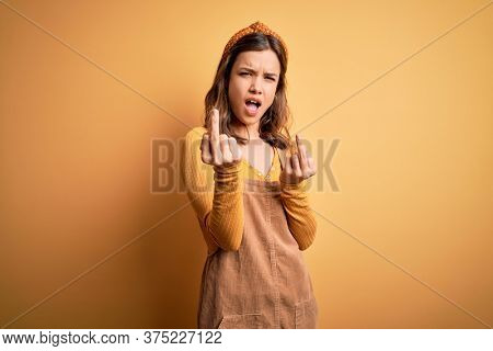 Young beautiful blonde girl wearing overall standing over yellow isolated background Showing middle finger doing fuck you bad expression, provocation and rude attitude. Screaming excited
