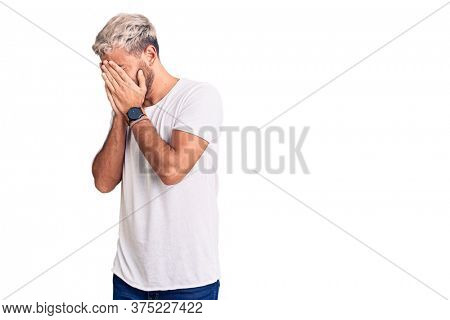 Young handsome blond man wearing casual t-shirt with sad expression covering face with hands while crying. depression concept.
