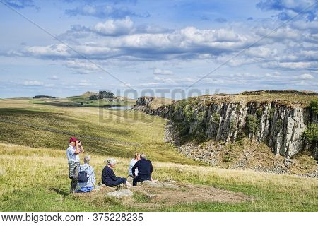 11 August 2018: Hadrians Wall, Northumberland, Uk - Group Of Gray Haired Seniors Sitting On The Gras