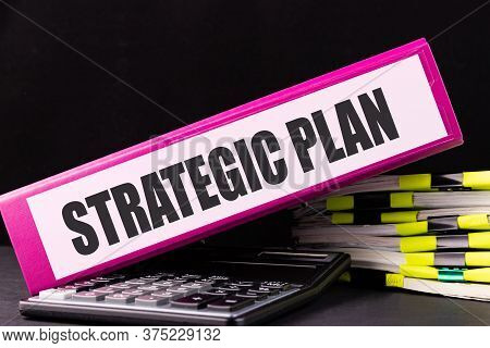 Strategic Plan Text Is Written On A Folder Lying On A Stack Of Papers On An Office Desk. Business Co