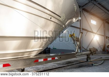 Big Luxury Cabin Motorboat Cruiser Yacht Launching At Trailer Ramp From Storage Boat Hangar Garage.