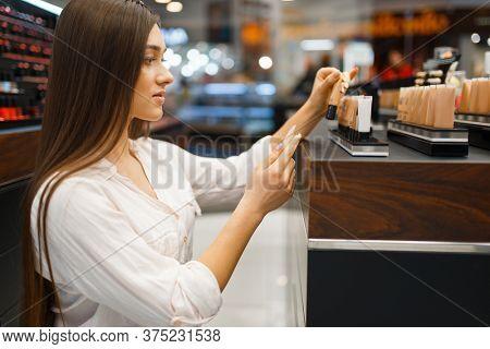 Beautiful woman at the shelf in cosmetics store