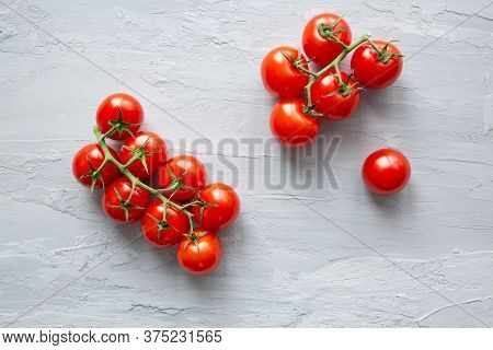 Fresh Red Cherry Tomatoes On Grey Concrete Background, Top View.