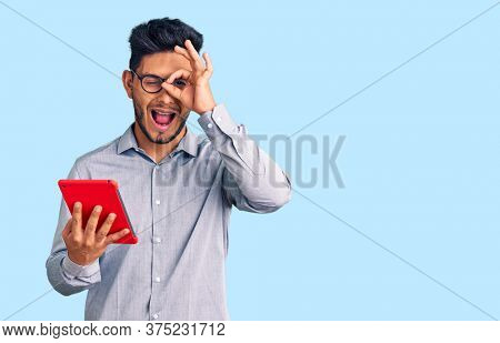 Handsome latin american young man holding touchpad smiling happy doing ok sign with hand on eye looking through fingers