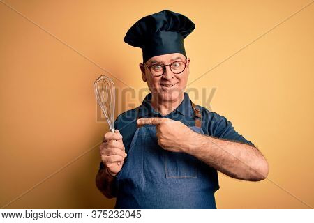 Middle age hoary cooker man wearing apron and hat holding whisk over yellow background very happy pointing with hand and finger