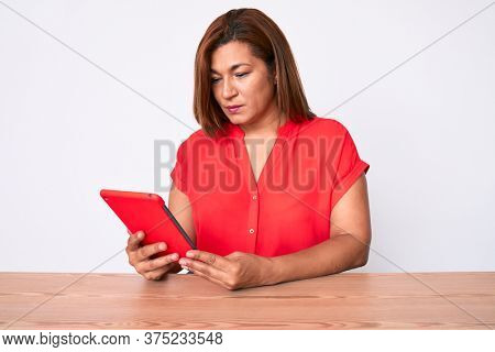 Middle age brunette hispanic woman using touchpad sitting on the table thinking attitude and sober expression looking self confident