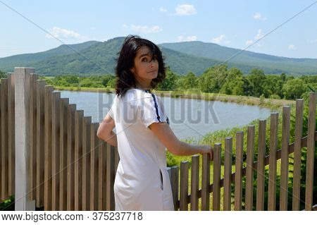 Portrait Of 45 Year Old Russian Brunette Woman Turned Back And Looking At The Camera. Windy Summer D