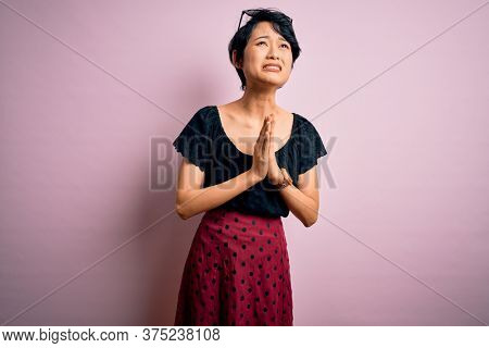 Young beautiful asian girl wearing casual dress standing over isolated pink background begging and praying with hands together with hope expression on face very emotional and worried. Begging.