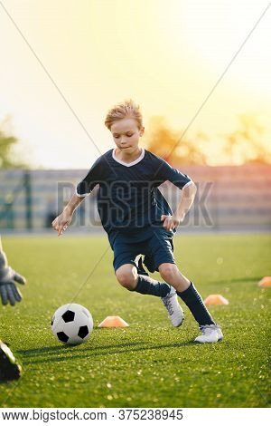Young Blonde Boy Kicking Soccer Ball On Drill. Kids Playing Football Training Game On The School Spo
