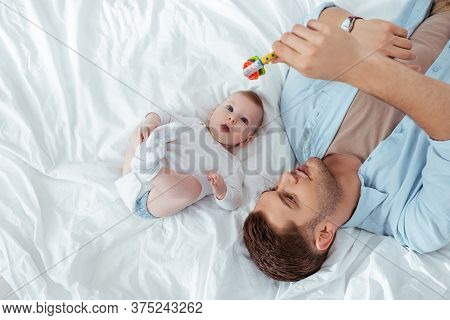 Top View Of Young Father Playing With Baby Rattle Over Cute Little Son Lying In Bed