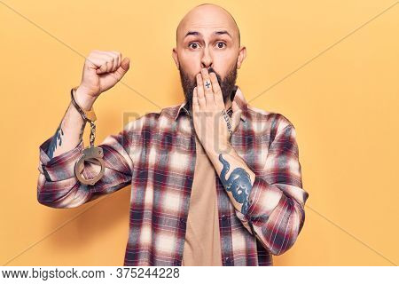Young handsome man wearing prisoner handcuffs covering mouth with hand, shocked and afraid for mistake. surprised expression