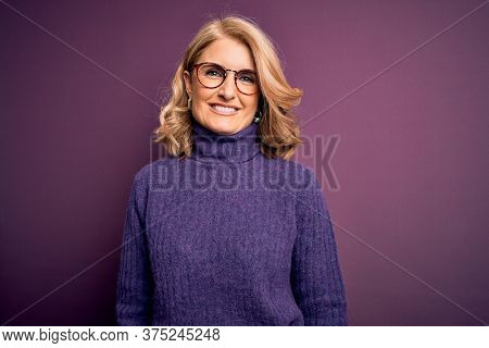 Middle age beautiful blonde woman wearing casual purple turtleneck sweater and glasses with a happy and cool smile on face. Lucky person.