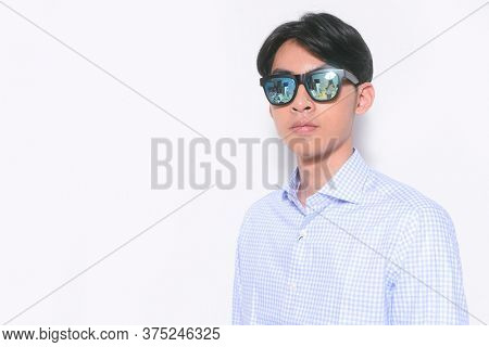 Young handsome casual man wearing sunglasses with striped long sleeved shirt