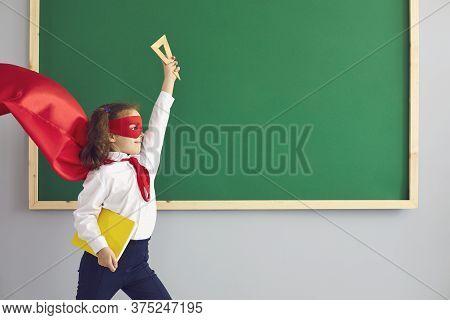 Back School. Cute Brave Girl In Superhero Costume Near Chalkboard At Classroom. Kid Wearing Hero Cap