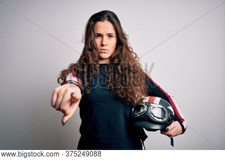 Beautiful motorcyclist woman with curly hair holding moto helmet over white background pointing with finger to the camera and to you, hand sign, positive and confident gesture from the front