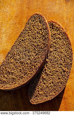 Slices Of Dark Rye Bread Lie On The Wooden Surface Of The Table Outdoors On A Sunny Day. Cooking Foo