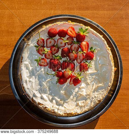 Cake With Young Strawberries In Cream Is On The Table On A Sunny Day In The Open Air. Spring Harvest