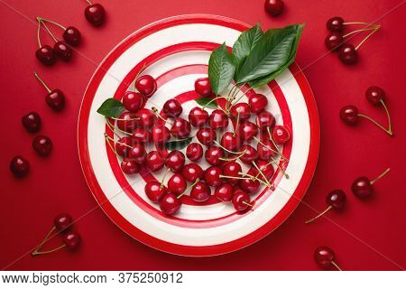 Fresh cherries with leaves on a red striped plate