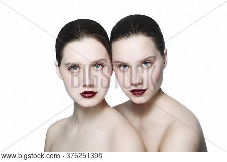 Portrait of two young beautiful girls with clean eye makeup and dark red lipstick