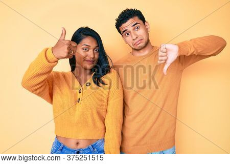 Beautiful latin young couple wearing casual clothes together doing thumbs up and down, disagreement and agreement expression. crazy conflict