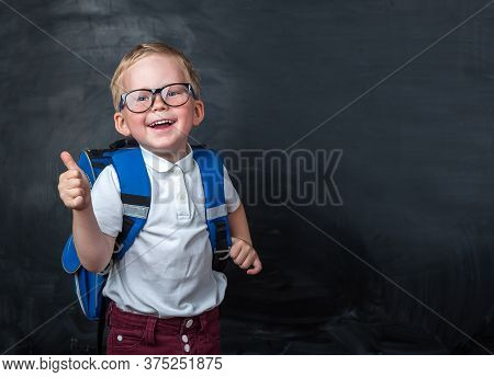 Happy Smiling Boy In Glasses With Thumb Up Is Going To School For The First Time. Child With School