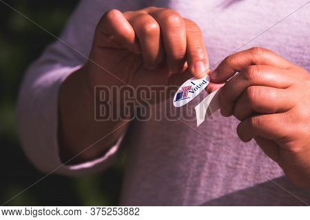 American Woman Peeling Sticker Off Of Backing To Place On Clothes To Communicate To Others That She
