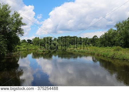 A Calm Lake View With White Clouds And Blue Sky Reflection
