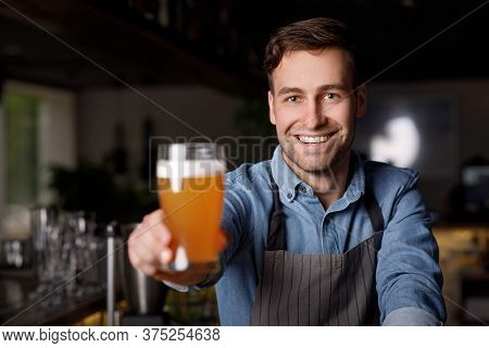 Work In Pub. Smiling Handsome Barman In Apron Holds Out Glass Of Delicious Beer In Interior Of Bar