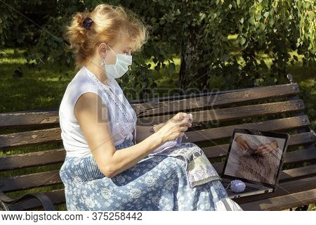 Woman With A Medical Mask On Her Face Is Sitting On A Park Bench Knitting Wool Clothes On Knitting N