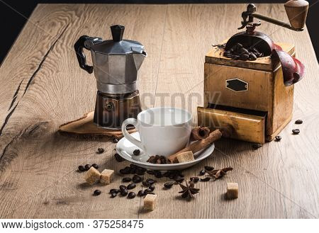 On Wooden Table Is A Coffee Maker Mocha, Vintage Coffee Grinder With Manual Drive. White Saucer With