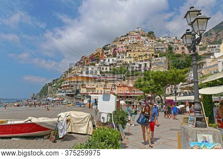 Positano, Italy - June 28, 2014: Tourists Walking At Promenade Near Sandy Beach At Summer Day In Pic